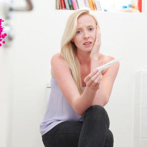 en ung kvinna som sitter på tuppen i ett badrum med ett graviditets test i handen och ser försktäckt ut