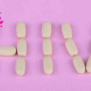 hiv ordet utskrivet med piller mot en ljusröd bakgrund