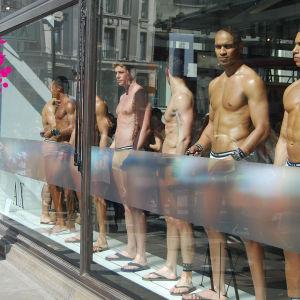 en gågata med män i boxers i ett skylttfönster