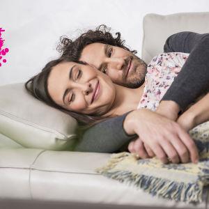 ett lyckligt par som ligger på en soffa och kramas