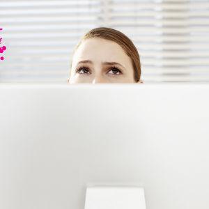en kvinnas bekymrade ögon som syns bakom en dator skärm