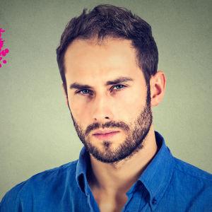 en man i mörkblå kragskjorta som ser tveksam ut