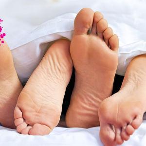 ett par av manliga och kvinliga fötter på varandra under vita lakan