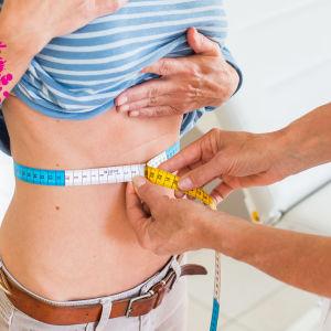 en flicka som är hos en doktor som mäter hennes midja med ett måttband