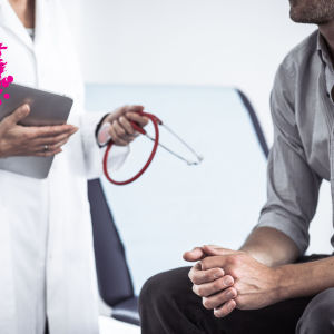 en man som sitter på ett läkar bord hos en läkare