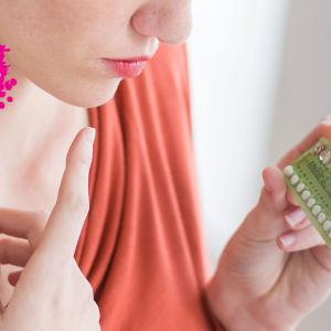 en ung kvinna som fundersamt ser på ett p-piller paket