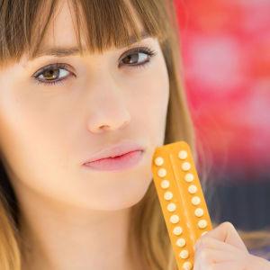 en ung kvinna som står med ett p-piller paket mot sin kind och ser seriös ut