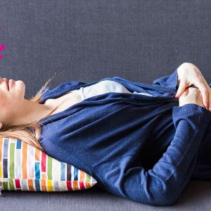 en vuxen kvinna som ligger på en soffa med sina händer placerade på sin nedre mage