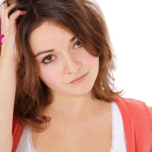 en ung kvinna som lutar sitt huvud på sin hand och ser tänkande ut