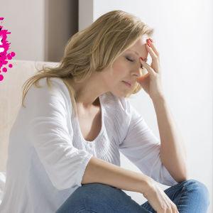 en kvinna som sitter på sin säng och lutar sitt huvud mot sin hand och ser missnöjd ut