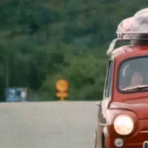En familj åker i en röd Fiat 500 på en landsväg. Takställiningen på bilen är fullastad