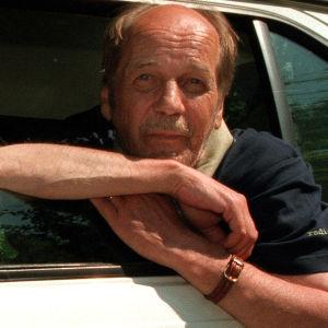 Liikennetoimittaja Esko Riihellä nojailee auton ikkunasta 1997.
