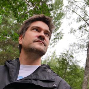 Kokki Henri Alén katselee metsässä.
