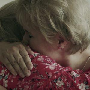 Kaksi naista halaavat toisiaan tiukasti