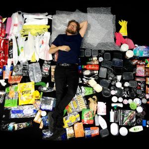 mies makaa muoviroskien päällä