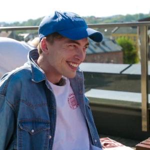 Markus Langen ler finurligt med keps på huvudet på en takterrass.