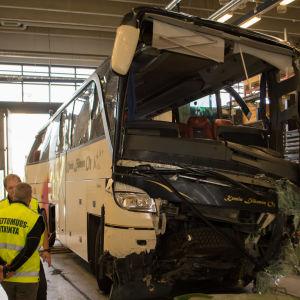 En buss i ett garage.Bussens framparti har omfattande skador.