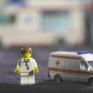 En leksaksdoktor som står bredvid en leksaksambulans på en filt.