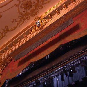 En röd ridå är uppdragen på Åbo Svenska Teater, bitar av det gulddekorerade taket på teatern.