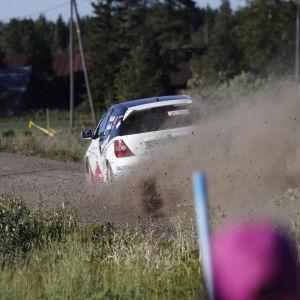 En rallybil kör i hög fart på grusväg och det bildas ett moln av grus bakom bilen.
