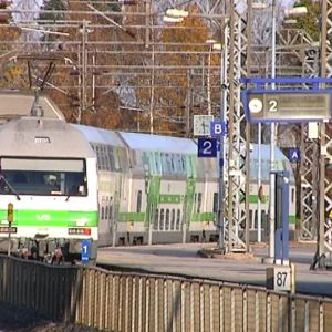 Ett grönt och vitt tåg åker iväg från perrongen.