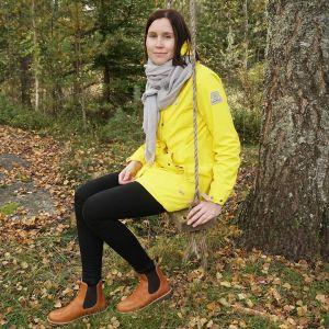 Kati Parkkinen istuu keinussa syksyisessä maisemassa
