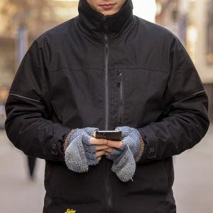 Mies selaa kännykkää Jyväskylän keskustassa.