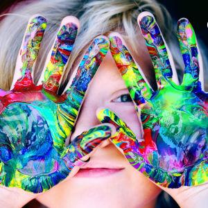 Pieni poika pitää kasvojensa edessä käsiä, joissa on sormivärejä.