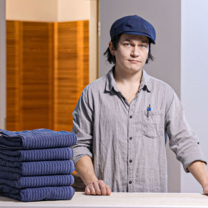 Mies katsoo kameraan, pöydällä sinisiä pyyhkeitä siistissä pinossa.
