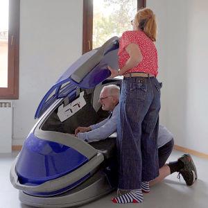 En man och en kvinna installerar en blå plastig självmordsmaskin som ser ut som en stor pulka med lock.