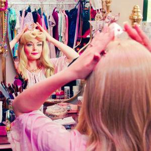 En dam klädd om Törnrosa sitter framför en spegel och lägger på en krona. Spegelbordet är fullt av smink och accessoarer.