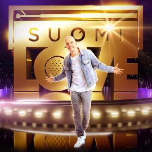 Elastinen seisoo SuomiLOVE logon edessä, päällään farkkutakki, farkut ja valkoinen t-paita.