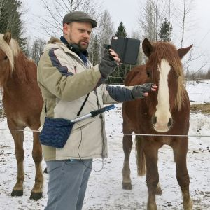 Olli poseeraa hevosten kanssa