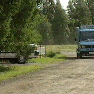 Vaaleansininen jäätelöauto ajaa hiekkatiellä 1995.