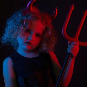 Pieni tyttö ob pukeutunut paholaiseksi, päässä on sarvet ja kädessä leikkihiilihanko.