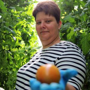 Smith's Gardenin viljelijä Johanna Smith pitelee tomaattia