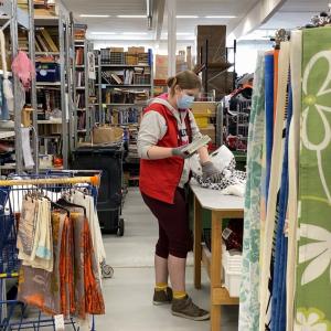 SPR:n Kontin työntekijä seisoo pöydän ääressä tyhjentämässä muovipussia, jossa lahjoitustavaroita. Ympärillä valtavat kasat Kontille lahjoitettua tavaraa, kuten verhoja ja kirjoja