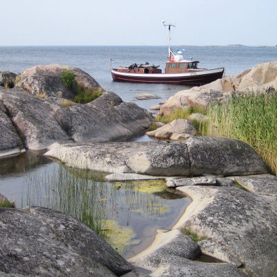 Kallioinen merenranta ja vene.
