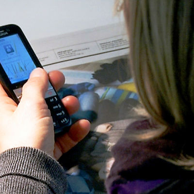 Lehdenlukija näppäilee kännykkää
