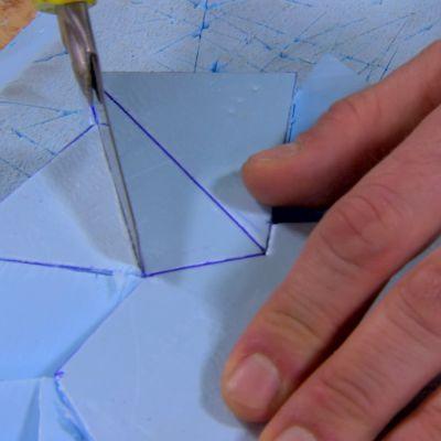 Jim använder en mattkniv för att skära i polystyrenet.