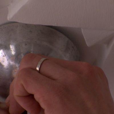 Jim installerar lampan under takrosetten.