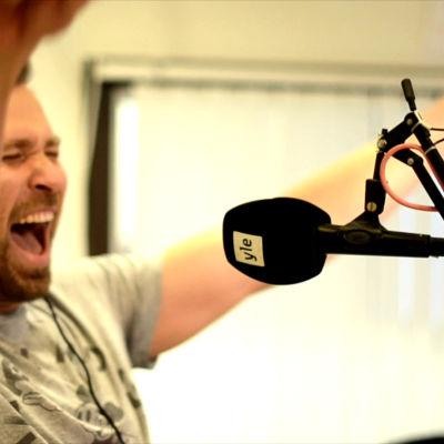 mange e skitglad , skriker in i en mikrofon i en radiostudio