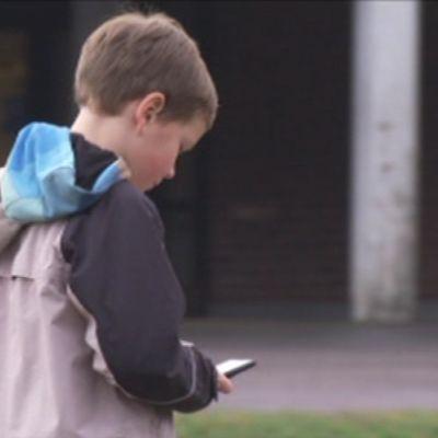 poika katsoo matkapuhelinta