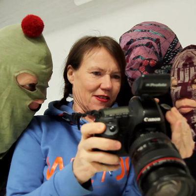 Rosa Liksom katsoo kuvia kamerasta kuvattaviensa kanssa
