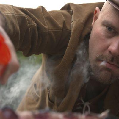 Toimittaja Totti Toivonen laittaa suolaa grillikyljen päälle pikkusikari suussaan.