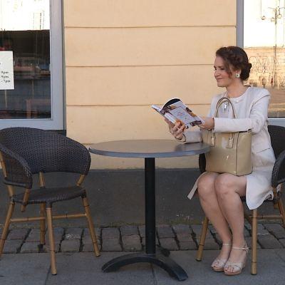 Pia-Maria Lehtola sitter på ett utecafé och läser Mirva Saukkolas nya stilguide.