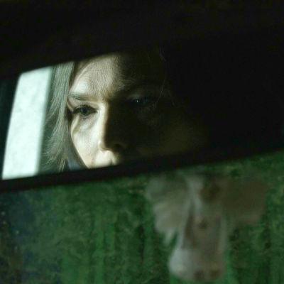 Kvinnas ansikte i backspegeln på en bil.