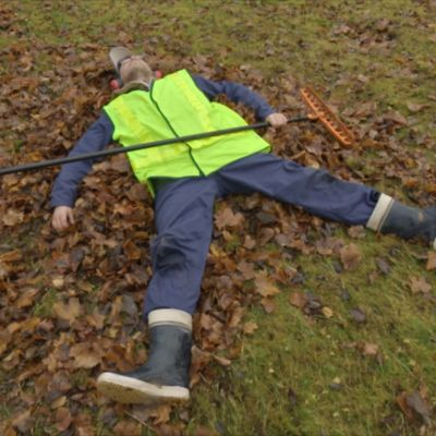 Puistotyöntekijä makaa syksyllä lehtikasan päällä