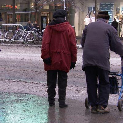 Ikä-ihmisiä odottamassa kadunylitysvuoroaan kaupungissa.