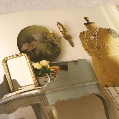 En spegel med guldram och en antik torso.